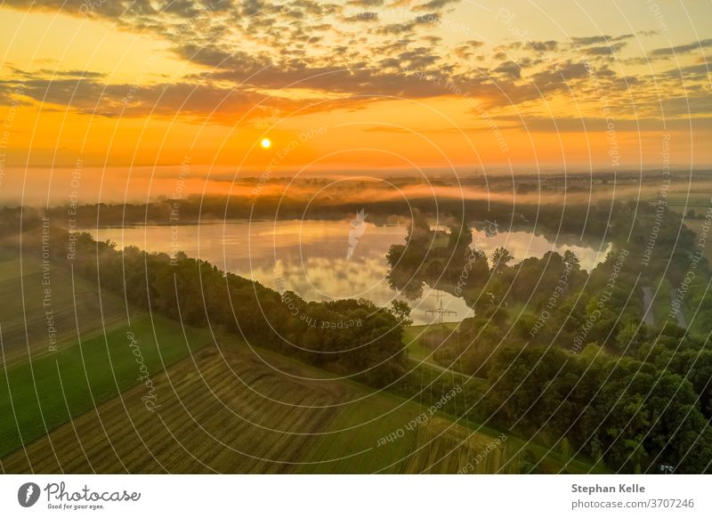 Germany, a powerful sunrise over a misty lake, pure nature moment. morning field sky background summer glow fog tree water orange beautiful landscape view