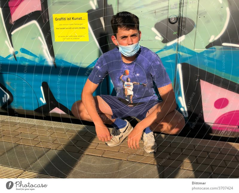 Young man likes graffiti but has insufficiencies in wearing masks younger Graffiti Face mask Platform Russian squat mouth-nose protection