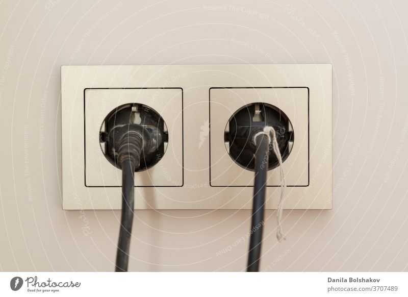two black plugs are plugged into a double electrical outlet with a frame technical electronics extension cord power supply two pin plug power line power cable