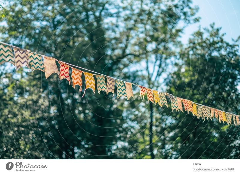 A colourful pennant chain between trees at a garden party Party bung Adorned Decoration Birthday Childrens birthsday Paper chain Feasts & Celebrations Embellish