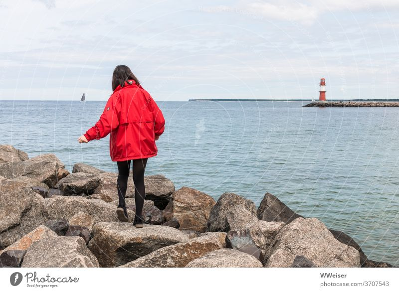 Young girl balances on the big stones of the western pier Young woman Balance Boulders Mole Wetsmole Warnemünde Rostock Lighthouse Baltic Sea Harbour Sky Red