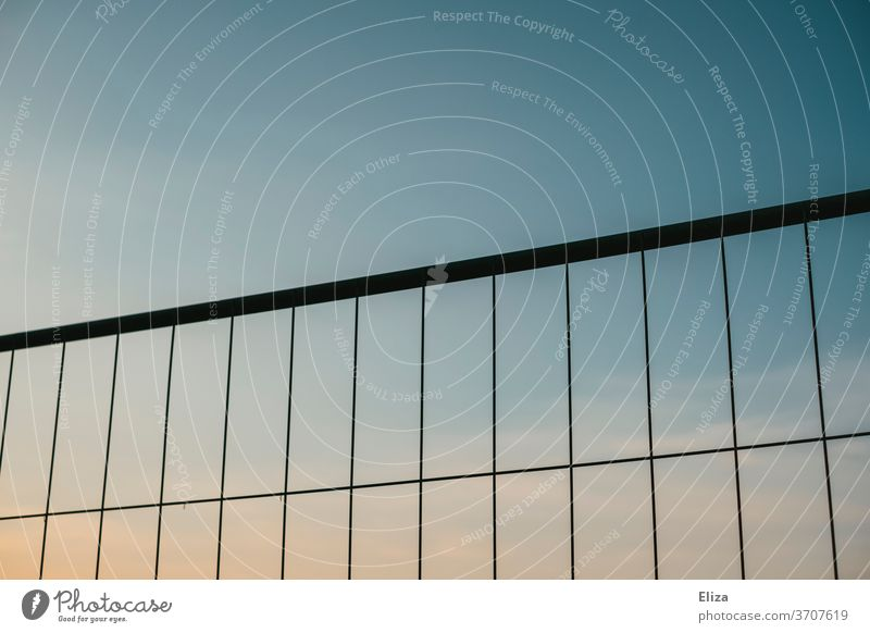 Building fence before evening sky Hoarding Sky Fence Barrier Grating Metal Construction site Structures and shapes Metalware cordon Safety Abstract