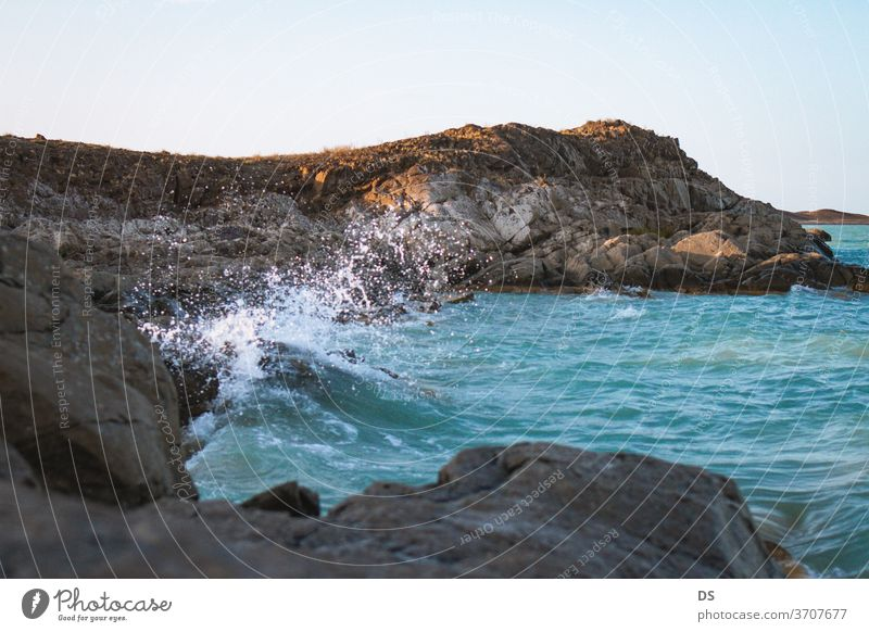 Mountains In The Sea At Sunset scenic shore seascape wave beauty view outdoor island tourism background stone beach coastline sky beautiful rock ocean landscape