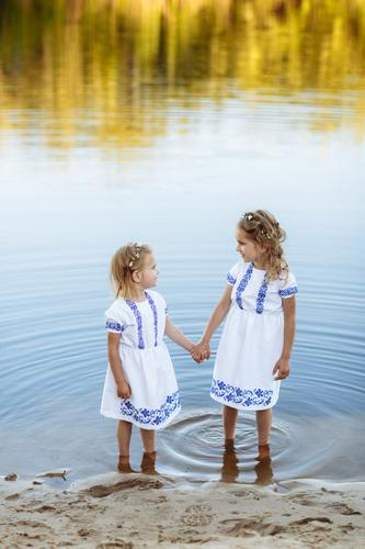 Two adorable little sisters laughing and hugging on warm and sunny summer day. two sisters in white dresses near the water. child family girl friend kid enjoy