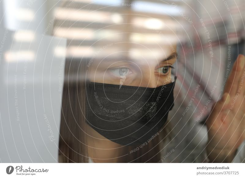 young woman in a medical mask behind a windows glass at home. concept of quarantine of the coronavirus pandemic, covid 19. selective focus room epidemic illness