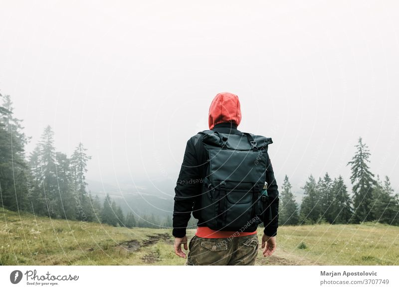 Nature explorer enjoying the view of  a foggy mountain range adventure alone backpack backpacker environment exploring forest freedom green hike hiker hiking
