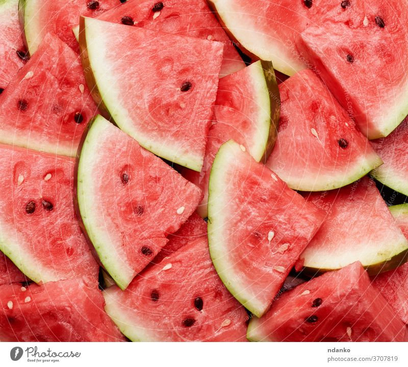 many sliced terrugol pieces of ripe red watermelon with brown seeds food background healthy sweet nature freshness juicy dessert summer snack diet closeup