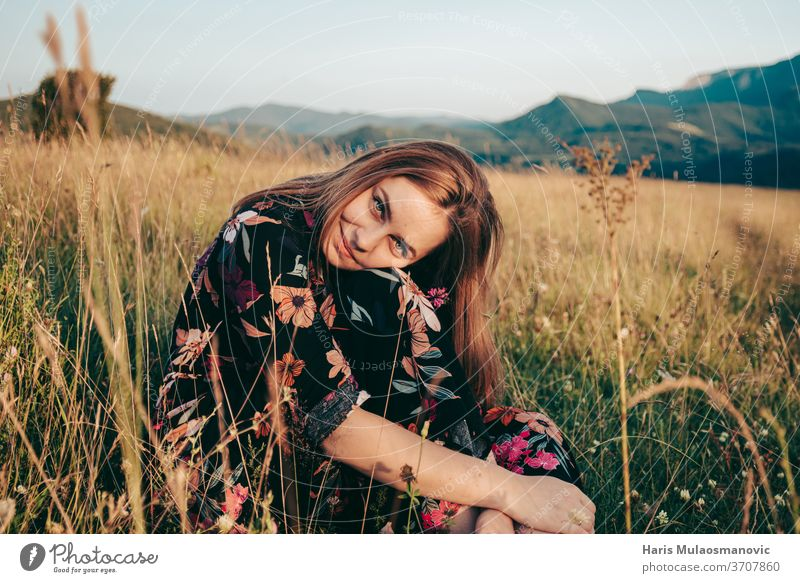 Happy woman sitting in grass field with mountains in background in sunset adventure beautiful beauty brown caucasian cute dress female flower freedom girl