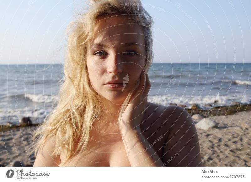 Portrait of a young blonde woman in front of the Baltic Sea Young woman Woman girl 18-20 years Blonde Slim already Curly sensual natural green eyes long hairs