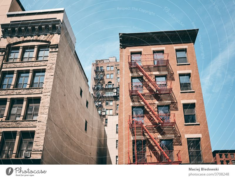 Old tenement house with fire escapes, New York City, USA. Manhattan building apartment city facade old vintage stairs NYC filtered brick ladder residential