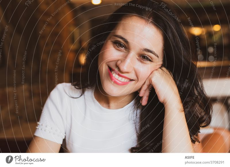 Portrait of a beautiful cheerful girl in a cafe looking at you young woman portrait happy smile person joy bar people toothy face close up brunette spanish