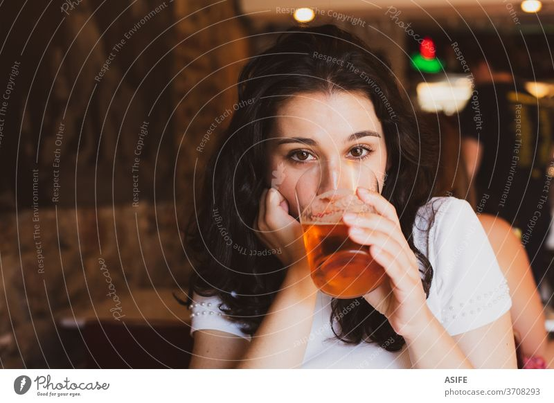 Young beautiful woman drinking beer in a glass in a bar girl young portrait summer cheers chill cold alcohol happy smile enjoy pub person people toothy face