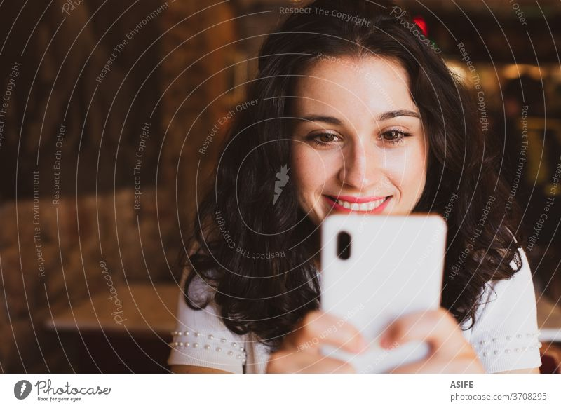 Happy young beautiful woman using her smartphone in a bar girl cafe portrait happy smile person joy people toothy face close up mobile phone smart phone