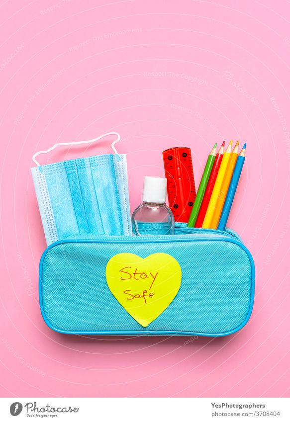 Pencil case with face mask, sanitizer and crayons. School supplies with stay safe message back back to school background blue care concept copy space corona