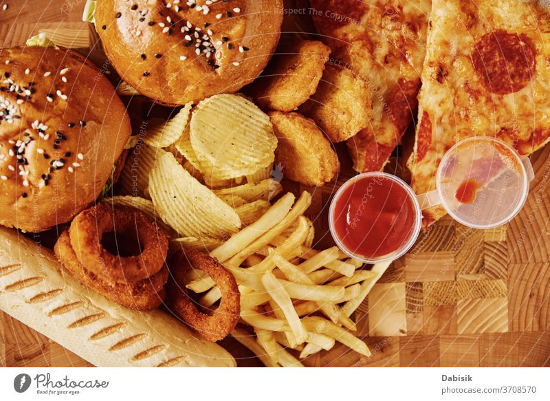 Unhealthy and unhealthy food. Different kinds of fast food on the table, close-up Food swift Junk Fat Table American Meal Eating Restaurant Pizza Diet Hot