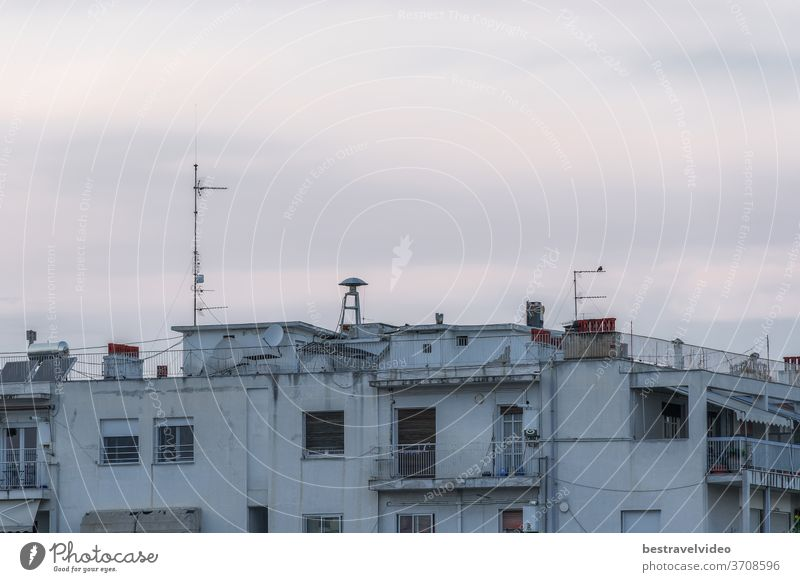 War air raid siren on residential buildings rooftop. Evening view of old mushroom shaped attack warning siren, between antennas and satellite dishes on top of city houses in Thessaloniki, Greece.
