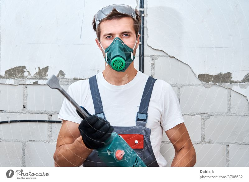 Renovation concept. Man in builder uniform with hammer drill make repairs in the room renovation man handyman protection construction male wall worker