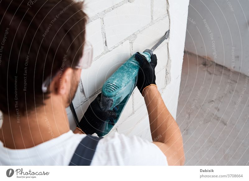 Man with demolition hammer removes stucco from wall. Concept of the renovation outline Hammer Drill by hand Construction Equipment work Tool Industry Machinery