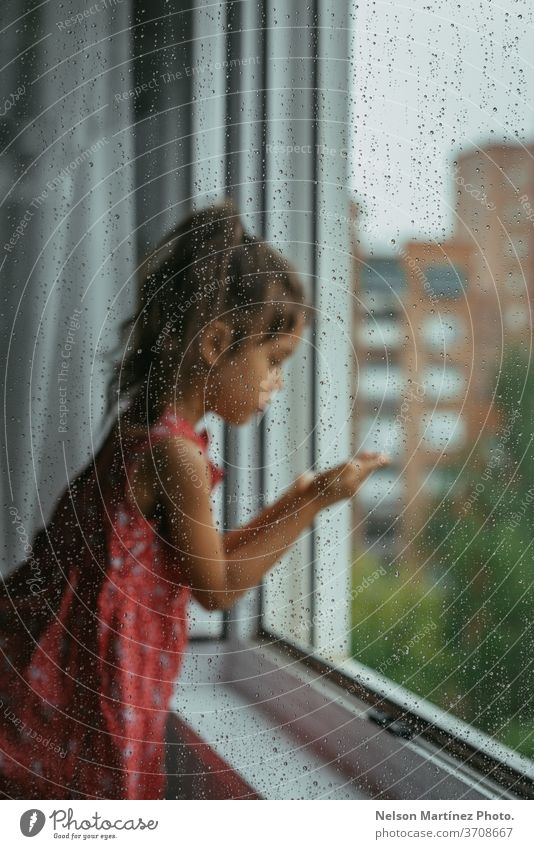 Little girl looking through the window in her bedroom in a rainy day. She is standing in a white chair, backward. We can see drops in the crystal. red child