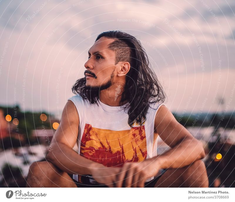 Portrait of hispanic male with long hair. We can see the city with a bokeh background. isolated person white adult proud front man casual lifestyle cool
