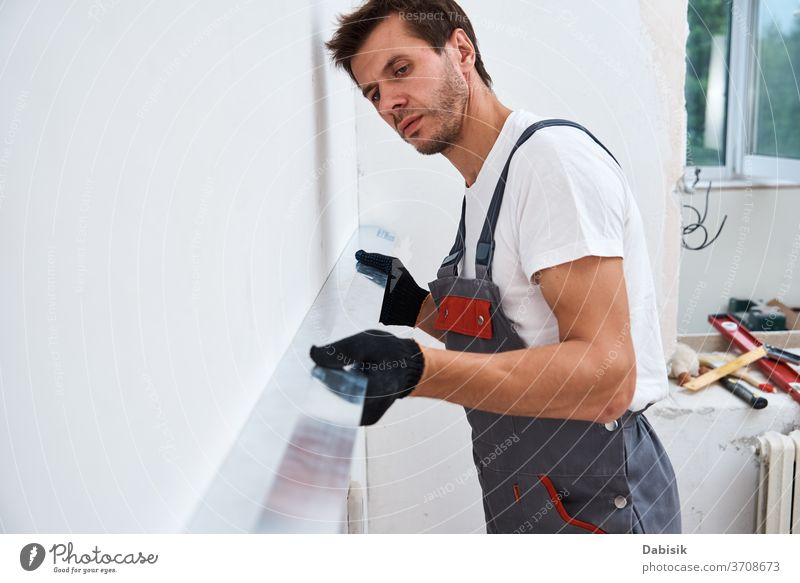 Renovation concept. Male worker plastering a wall using a long spatula renovation man tool stucco industry manual repair construction improvement home building