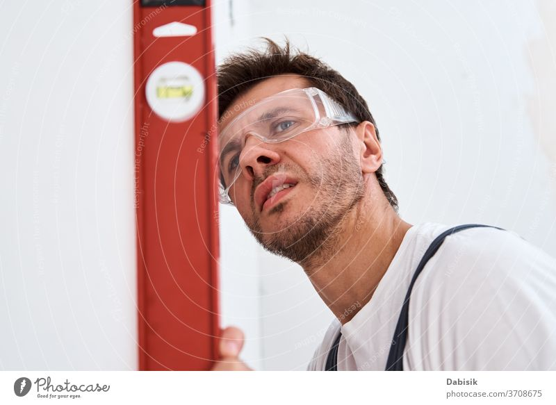 Renovation concept. Male worker checking level of the wall with the bubble level tool renovation man repair handyman construction home job professional manual