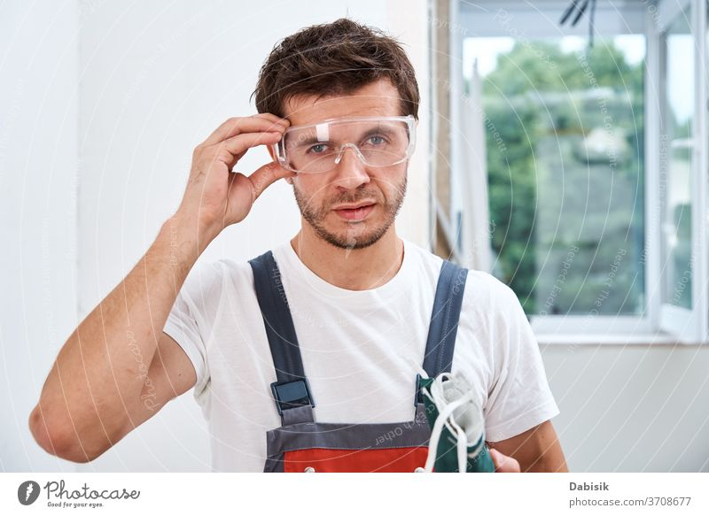 Portrait of home repair worker. Renovation handyman with protective glasses and respirator renovation protection builder construction male design wall
