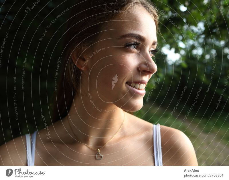 Lateral, close portrait of a young woman in nature Light Athletic Feminine Emotions emotionally Looking into the camera Central perspective