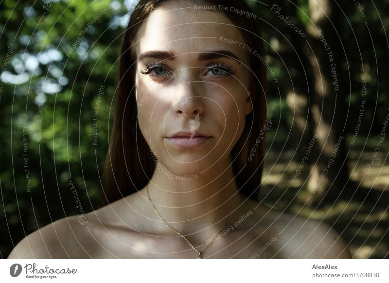 Close portrait of a young woman in the forest Light Athletic Feminine Emotions emotionally Looking into the camera Central perspective Shallow depth of field