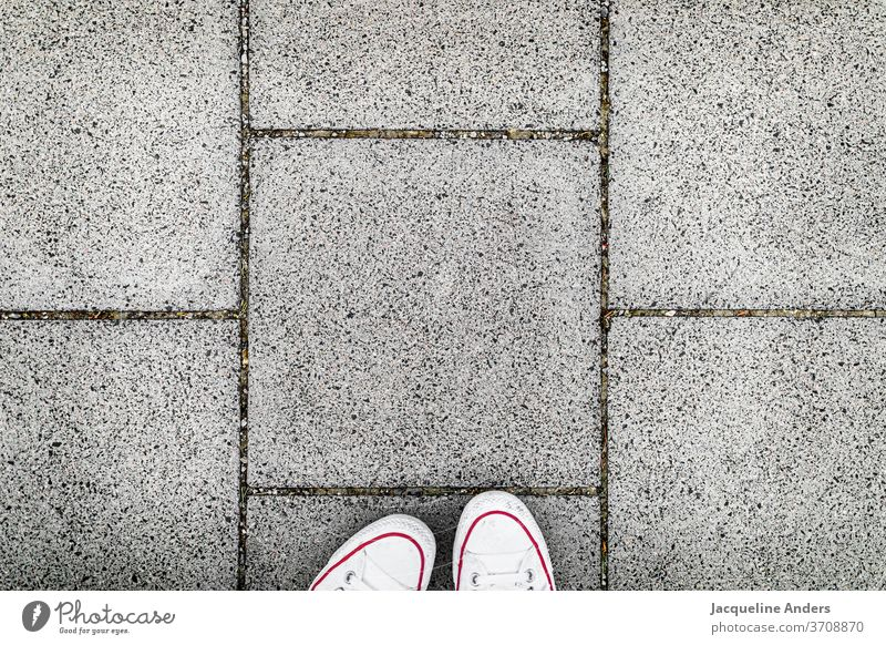 Walking on the sidewalk Street off walkway slabs Footpath Footwear foot Downward Asphalt Stand Woman Exterior shot Gray White Day Human being shape Pattern