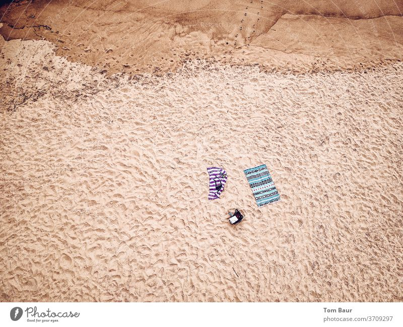 Two bath towels on the beach from the bird's eye view Beach Sand traces in the sand Lonely UAV view droning Bird's-eye view Tracks Coast Barefoot