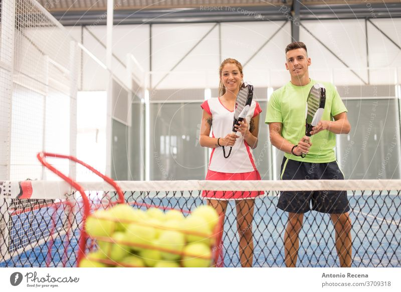 Couple playing paddle tennis in blue court padel pádel sport sports recreation class man woman women lifestyles training shot couple net ball leisura people