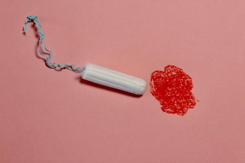 Tampon moving towards red painted spot. Menstruation, blood, period, menstrual flow. symbol picture Hemorrhage Reconnaissance symbolism Feminine Colour photo