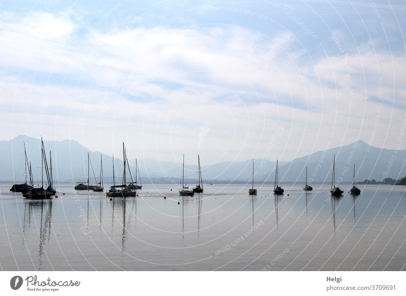 in the morning at the Chiemsee - many sailing boats are waiting for their deployment in the morning on the Chiemsee, reflections in the water, mountains in the background, blue sky with clouds