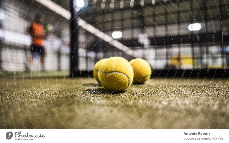 Paddle tennis balls in court paddle tennis padel sport game tournament man blurred indoors fences objects recreation leisure training sphere grass turf set net