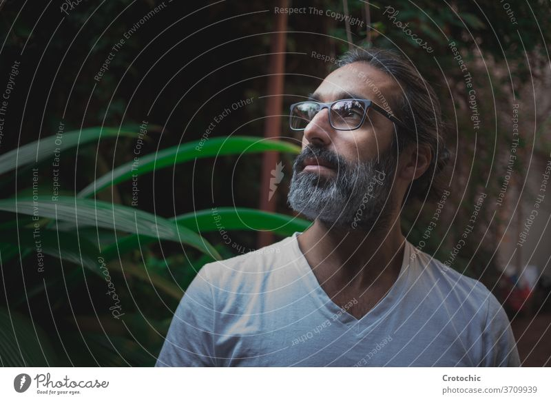Man with glasses facing sideways in the middle of a garden with a relaxed expression senior intellectual zen spiritual meditation white guru long tied turn