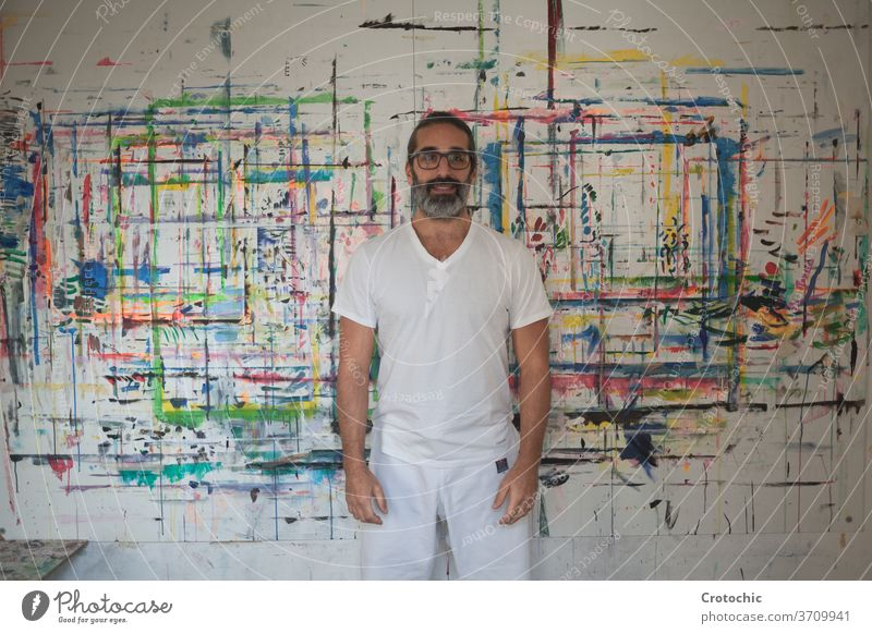 Man dressed in white standing in front of a picture artist creativity individuality indoors paintbrush photography skill portrait adult passion pride beard