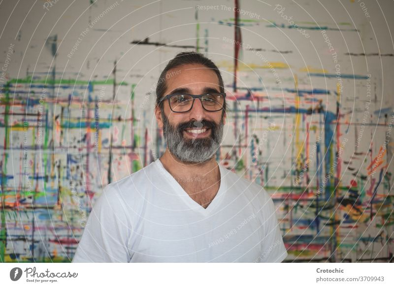 Portrait of a man dressed in white standing in front of a picture artist creativity individuality indoors paintbrush photography skill portrait adult passion