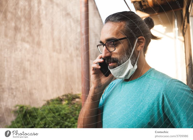 Man with glasses talking to his mobile phone with his mask down unsafe mistake unprotected hold communication sound voice covid coronavirus breath epidemic