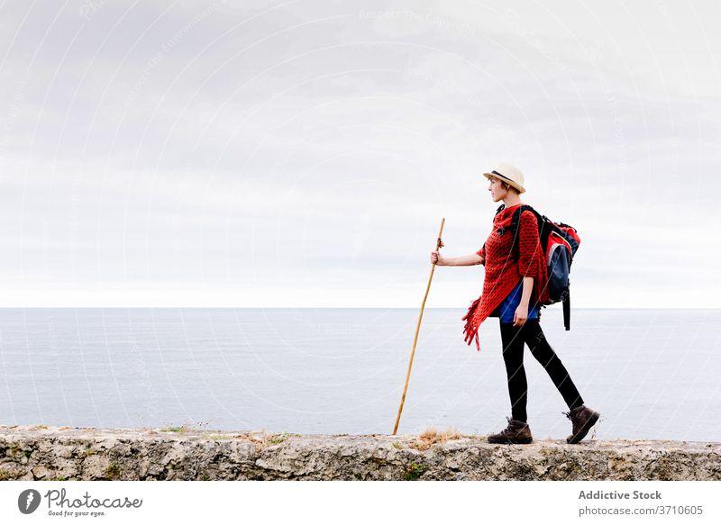 Happy traveler with trekking stick enjoying freedom hiker backpacker woman happy pilgrimage nature activity camino de santiago spain cliff female asturias