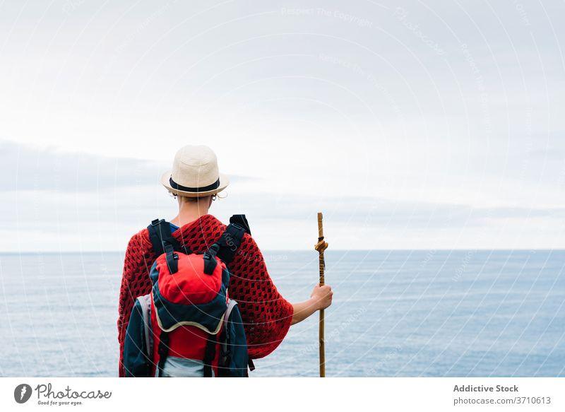Anonymous traveler with trekking stick enjoying freedom hiker backpacker woman happy pilgrimage nature activity camino de santiago spain female asturias llanes