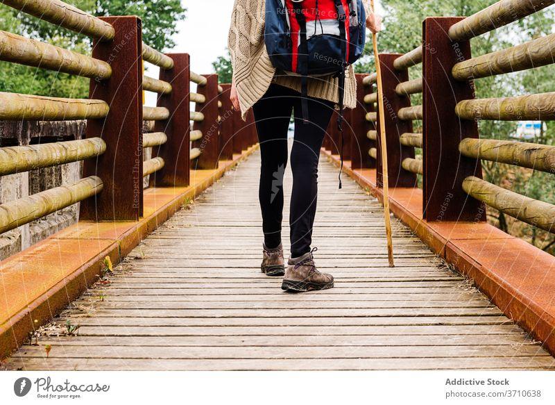 Hiker walking on wooden bridge hiker traveler pilgrimage way path stick backpacker trekking activity lonely camino de santiago spain asturias llanes lifestyle