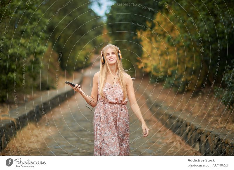 Smiling woman with smartphone and headphones walking in park happy listen using music summer enjoy young female browsing alley path device gadget lifestyle