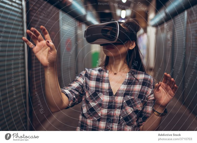 Woman in glasses of virtual reality in city vr woman experience grunge underground touch technology goggles using female shabby street narrow calm simulate