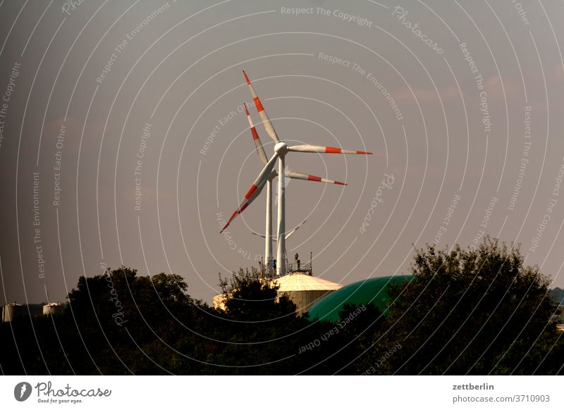 About two wind turbines in a row Highway Small Town soest urban wind power Pinwheel holidays Summer vacation Sky blue clear farsightedness Horizon