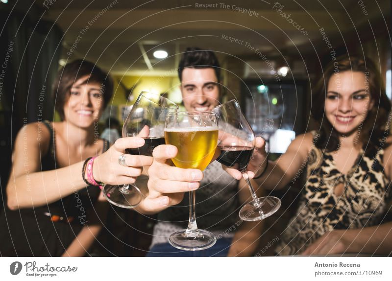 Three friends in restaurant with alcohol cups making toast to the view bar beverages adults caucasian beer wine drink drinking Eating women woman 25-30 years