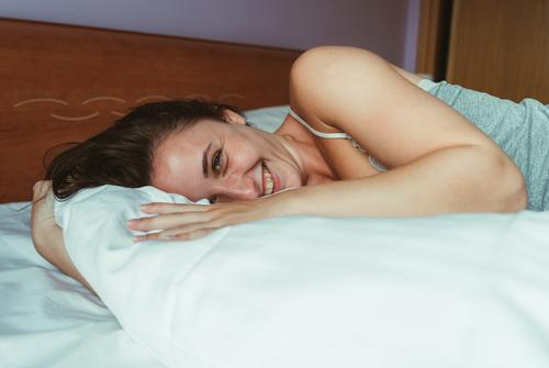 Close up portrait of a smiling attractive woman lying down on bed and looking at the camera. people adult one girl room bedroom family brunette at home