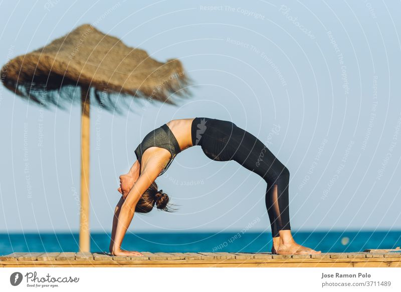 young woman doing yoga bridge exercise on the beach in front of the sea next to umbrella on people meditation person sport fitness relaxation wellness life sand