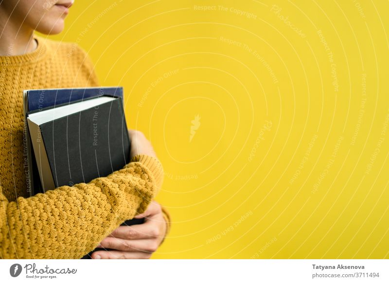 Student with books on yellow Woman schuler Education Book university University Yellow Reading Sweater Knitted person more adult studying people portrait Know