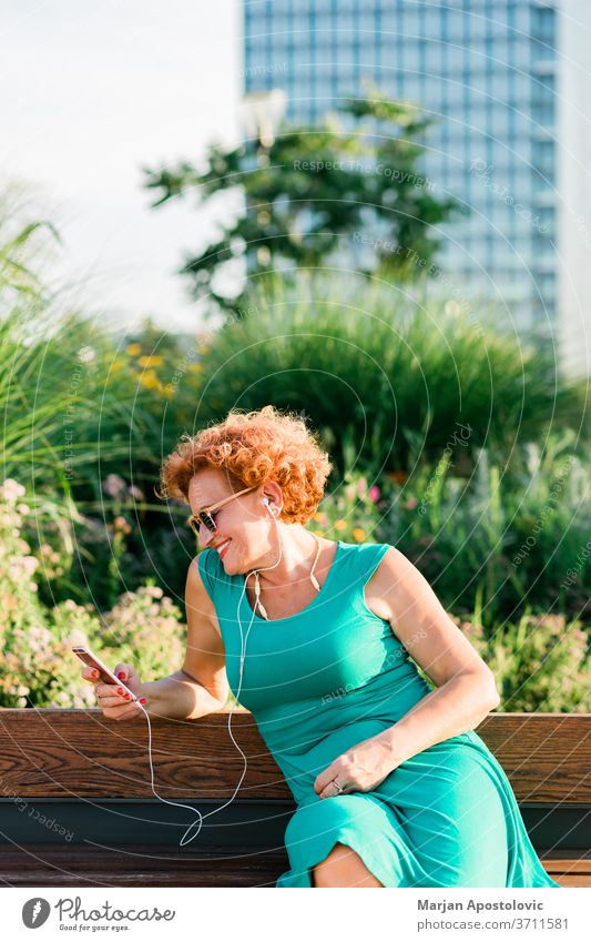 Mature woman listening to the music on her smartphone in the park 60s adult age aged beautiful bench casual caucasian cheerful city connectivity earphones